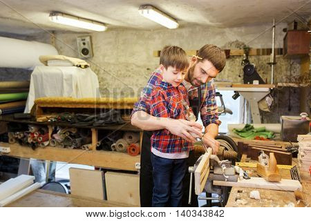 family, carpentry, woodwork and people concept - father and little son with hammer and chisel working with wood plank at workshop