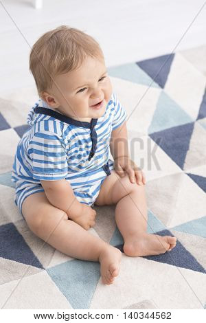 Shot of a little baby sitting on a floor with a grimace on his face