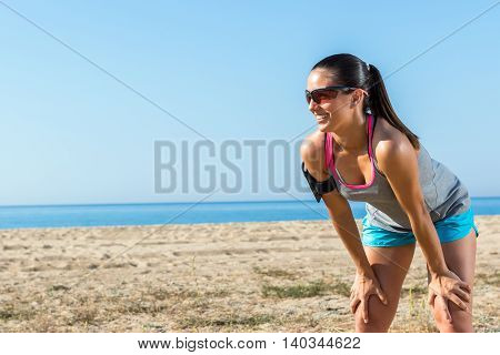 Close up of attractive young girl jogger taking a rest.Woman standing with hands on knees at beach front.