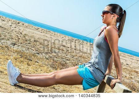 Full length portrait of attractive muscular female runner warming up at sea side.