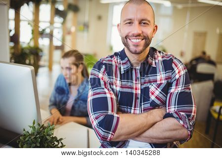 Portrait of smiling businesman with female colleague in background at creative office