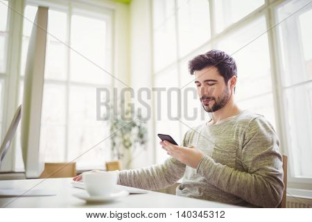 Businessman using mobile phone while working in creative office