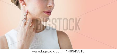 glamour, beauty, jewelry and luxury concept - close up of beautiful woman with golden ring and diamond earringover beige background