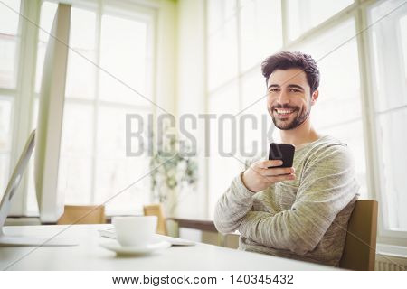 Portrait of smiling businessman holding mobile phone at desk in creative office
