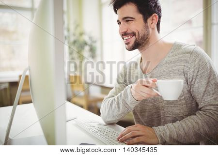 Smiling businessman holding coffee cup while working at desk in creative office