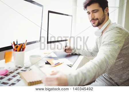 Young businessman working at desk in creative office