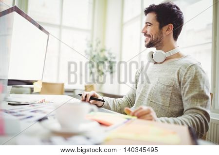 Young smiling businessman working on computer in creative office
