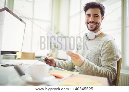 Portrait of smiling businessman holding papers in creative office