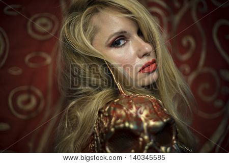 Sweet, blonde dressed in red armor gold on red art nouveau flourishes