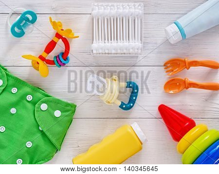 Collection of items for babies: cloth diaper, baby powder, nibbler, cream, teether, soother, cotton swabs, baby spoon and fork, pyramid toy on white wooden background. Top view or flat lay