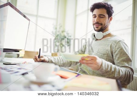 Young businessman writing from note in creative office