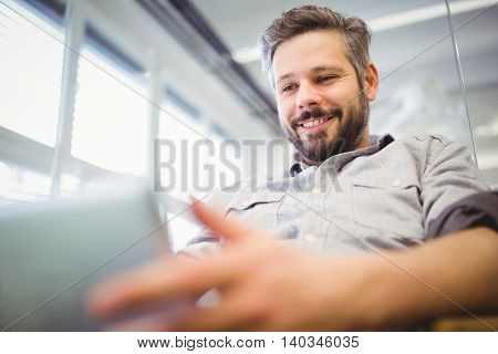 Low angle view of smiling businessman working on laptop in creative office