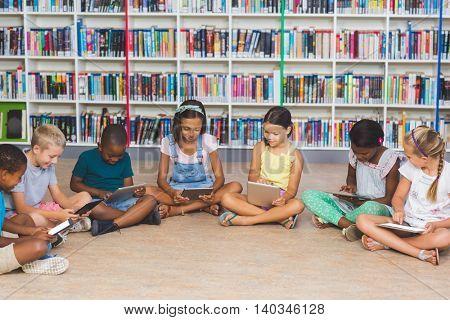 School kids sitting on floor using digital tablet in library at elementary school