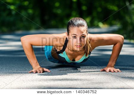 Close up portrait of fitness girl doing push ups against green background outdoors.