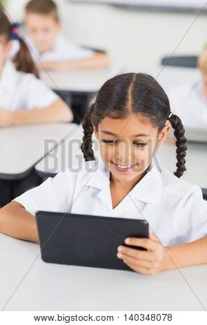 Schoolgirl using digital tablet in classroom at elementary school