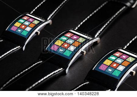 modern technology, object and media concept - close up of black smart watch set with menu icons on screen