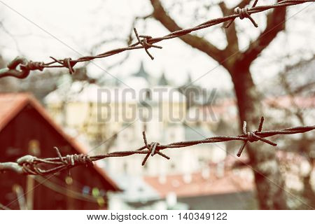 Barbed wire fence in old town Banska Stiavnica Slovak republic. Security theme. Yellow photo filter. Travelling in Europe. Private property.