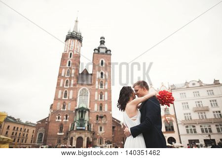 Elegant beautiful wedding couple walking on the main square in Krakow.