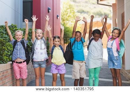 Group of happy kids standing in a row with hands raised at school campus