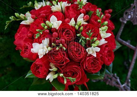 dense red bouquet of roses, with red berries and decor. Close