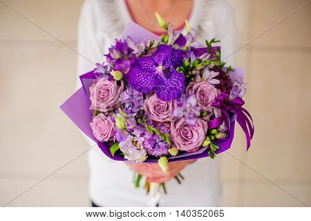Bouquet with purple orchids, roses, Hydrangea and other flower in hands