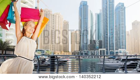 people, holidays, tourism, travel and sale concept - young happy woman with shopping bags over dubai city skyscrapers background