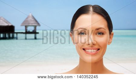 people, suntan, travel and summer holidays concept - close up of beautiful smiling woman with half face tanned over exotic tropical beach with bungalow background