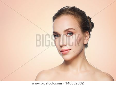 beauty, people and health concept - beautiful young woman face over beige background