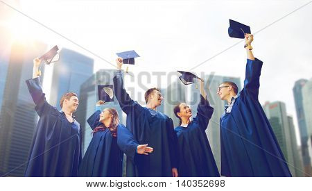education, graduation and people concept - group of smiling students in gowns waving mortarboards over skyscrapers background