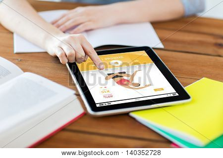 sport, education, technology and internet concept - close up of student woman with fitness application on tablet pc computer and notebook at home
