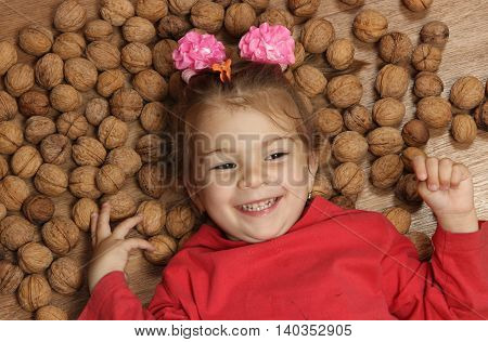 cheerful little girl lies on a floor on a heap of walnuts