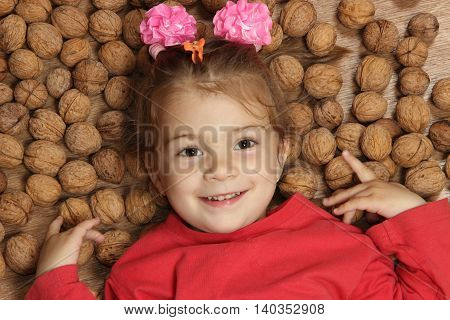 cheerful little girl lies on a floor on a heap of walnuts