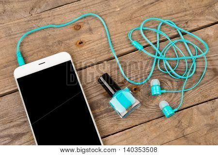 Blue Bottle Of Nail Polish, Smart Phone And Headphones On Brown Wooden Table