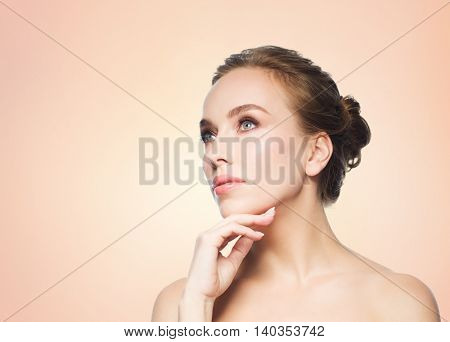 beauty, people and health concept - beautiful young woman touching her face over beige background
