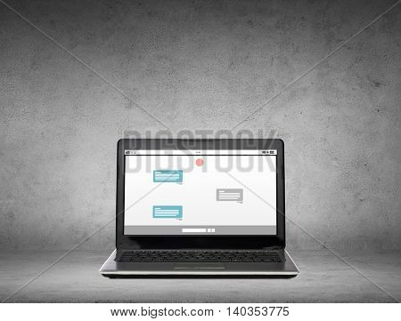 technology, internet and communication online concept - laptop computer with messenger chat on screen over gray concrete background