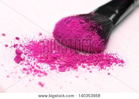 make-up brush on pink crushed eyeshadow .