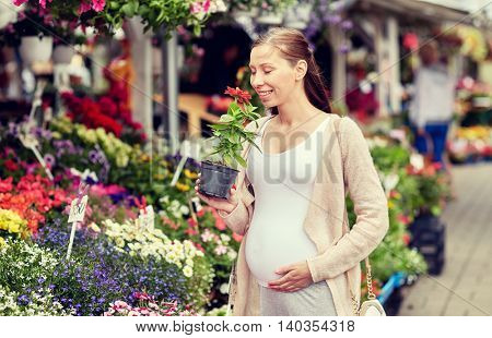 sale, shopping, pregnancy, gardening and people concept - happy pregnant woman choosing and smelling flowers at street market