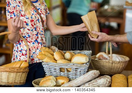 Mid section of woman purchasing bread in supermarket