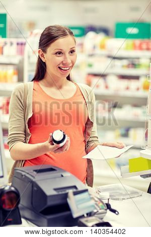 pregnancy, medicine, pharmaceutics, health care and people concept - happy pregnant woman with medication and prescription paper at pharmacy cash register