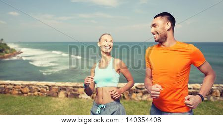 fitness, sport, exercising and healthy lifestyle concept - smiling couple running or jogging over sea or beach background