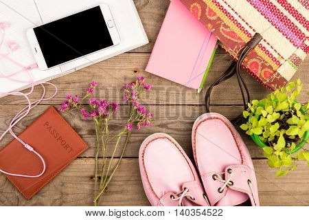 Straw Bag, Smart Phone, Headphones, Notepad, Pink Shoes, Passport And Book On Wooden Desk