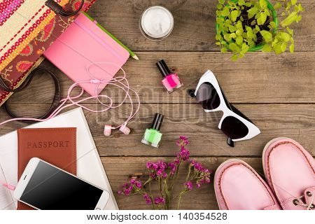 Straw Bag, Smart Phone, Headphones, Sunglasses, Notepad, Pink Shoes, Passport And Book On Wooden Des