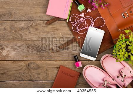 Brown Bag, Smart Phone, Headphones, Notepad, Pink Shoes And Passport On Wooden Desk