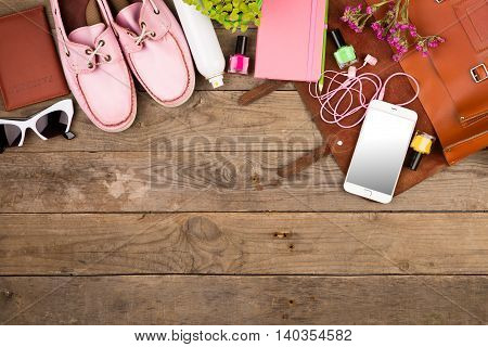 Brown Bag, Smart Phone, Headphones, Sunglasses, Notepad, Pink Shoes And Passport On Wooden Desk