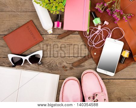 Brown Bag, Smart Phone, Headphones, Sunglasses, Notepad, Pink Shoes, Passport And Book On Wooden Des