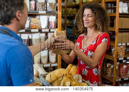 Male staff giving packed bread to woman in supermarket