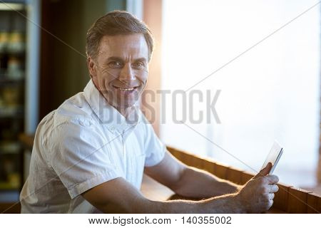 Portrait of smiling man using a digital tablet in café