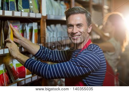 Portrait of male staff arranging grocery items on shelf in supermarket