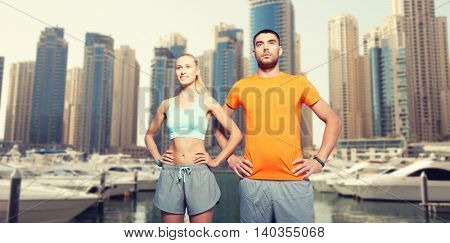fitness, sport, friendship and healthy lifestyle concept - happy couple exercising over dubai city street and harbor with boats background