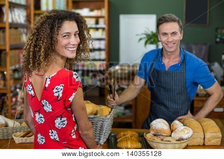 Smiling woman standing at bakery counter in supermarket